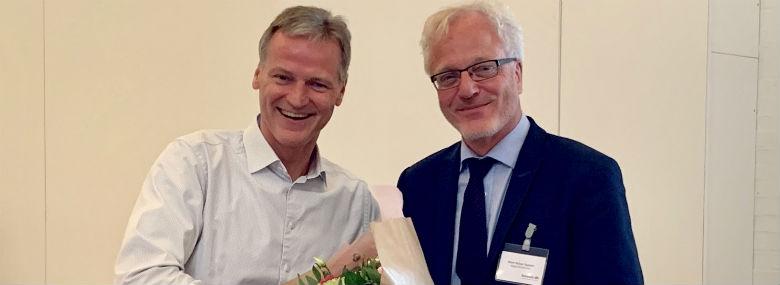 Med mere end 20 år på topposten i Vejle, er Niels Nybye Ågesen (th) én af de længst siddende kommunaldirektører i landet. Den erfaring skal nu i spil i rollen som formand for alle landets kommunaldirektører. På billedet lykønskes han af Komdirs afgående formand Henrik Kolind.<br />Foto: Komdir