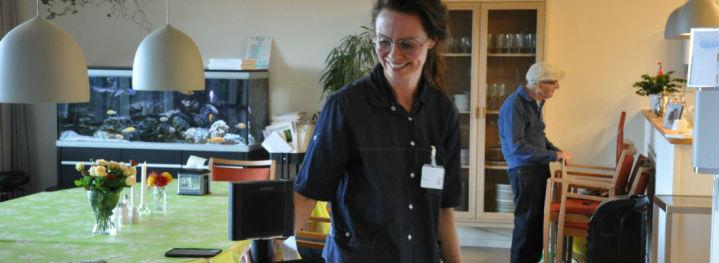 Sosu-assistent Lisbeth Møller triller rundt med iPad og højtaler på et stativ og er - efter lidt tilvænning - glad for at synge på sin arbejdsplads.<br />Foto: Emma Oxenbøll