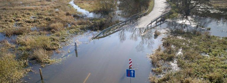 Gjern Å ved Sminge umiddelbart før dens udløb i Gudenå. Vejen er afspæret på grund af de store mængder vand på kørebanen i oktober 2019.<br />Foto: Morten Rasmussen, Ritzau Scanpix
